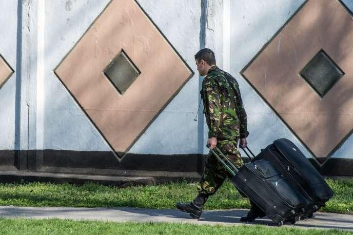 Un militaire ukrainien quitte sa base du port criméen de Feodossia, le 24 mars.