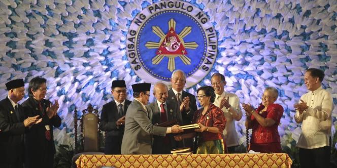 Le président philippin Benigno Aquino III (troisième en partant de la droite), Al Haj Murad Ebrahim (troisième en partant de la gauche) à la tête de Front Moro islamique de libération (FMIL), et le premier ministre malaisien, Najib Razak (au centre), lors de l'échange de l'accord de paix entre le gouvernement et la rébellion musulmane.