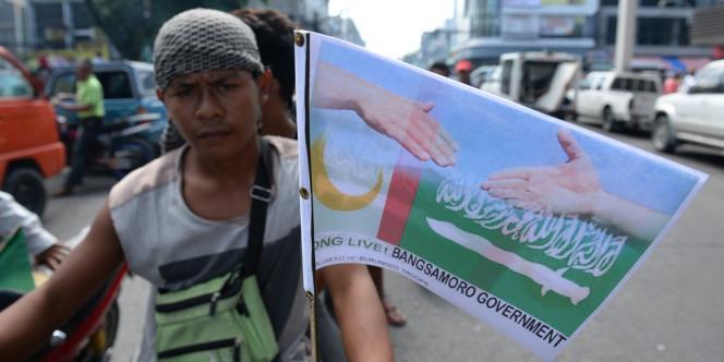 Un drapeau célébrant l'accord de paix et le gouvernement et le mouvement séparatiste musulman, attaché à la moto d'un habitant du sud des Philippines.