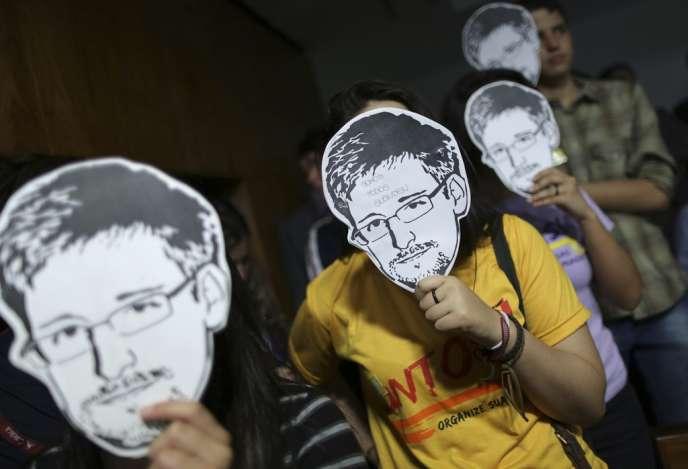 Manifestations contre les écoutes de la NSA en 2013. Des contestataires brandissent devant leur visage le portrait d'Edward Snowden, ancien analyste de l'Agence nationale de sécurité qui a révélé l'ampleur internationale de la surveillanc américaine.