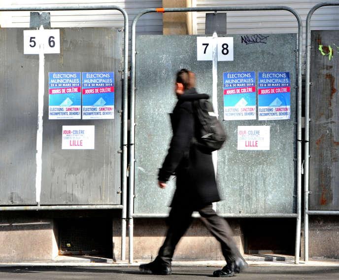 Devant des panneaux électoraux, à Lille, le 24 février 2014.