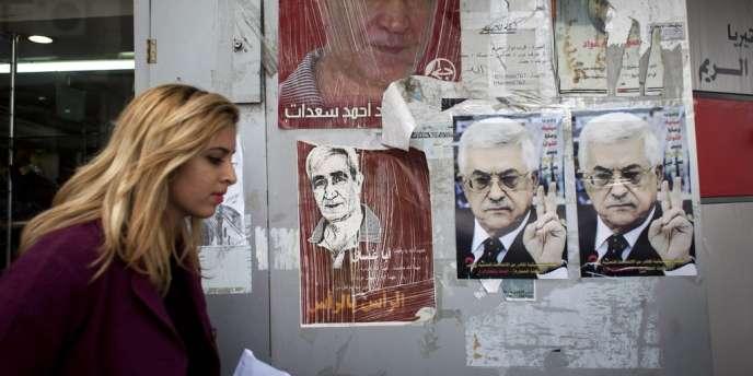 Dans une rue de Ramallah, une Palestinienne passe devant des portraits de Mahmoud Abbas et d'Ahmed Saadat, secrétaire général du Front populaire de libération de la Palestine,  le 19 mars.