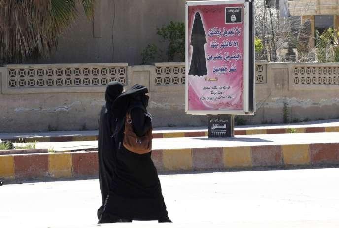 A Rakka, en Syrie, fief du groupe djihadiste Da'ech, un panneau portant des versets du Coran enjoint aux femmes de porter le niqab (voile islamique).