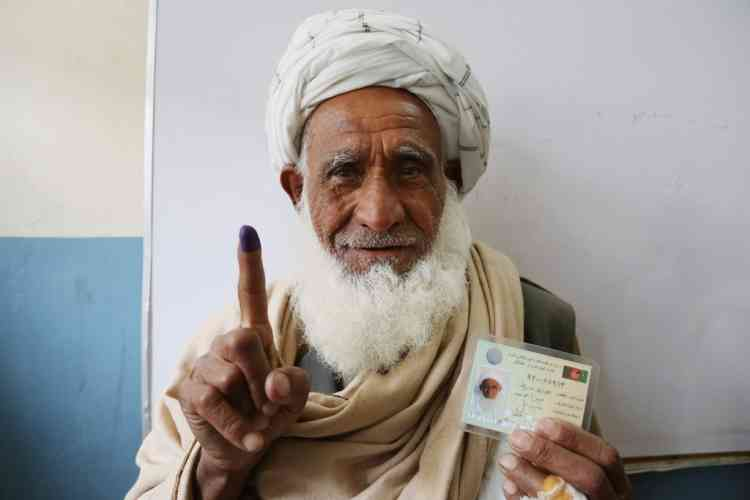 An Afghan man shows his inked finger after casting his vote at a polling station in Jalalabad, east of Kabul, Afghanistan, Saturday, April 5, 2014. Afghan voters lined up for blocks at polling stations nationwide on Saturday, defying a threat of violence by the Taliban to cast ballots in what promises to be the nation's first democratic transfer of power. (AP Photo/Rahmat Gul)