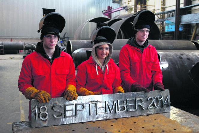 Trois jeunes ouvriers d'une aciérie de Renfrew présentent une plaque comportant la date du référendum sur l'indépendance.