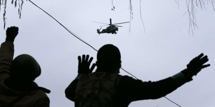 Des manifestants prorusses se rassemblent au QG occupé de la police de Sloviansk, survolé par un hélicoptère militaire, le 13 avril.