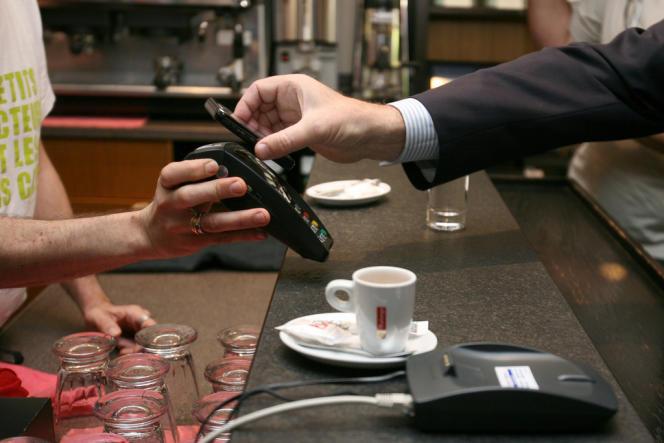 A Nice dans un café en 2010, un client paie avec son téléphone portable.