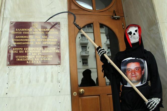 Un manifestant arbore un portrait du ministre de la santé grec Adonis Georgiadis, devant le bureau du ministère de la santé de Thessalonique, le 11 avril.