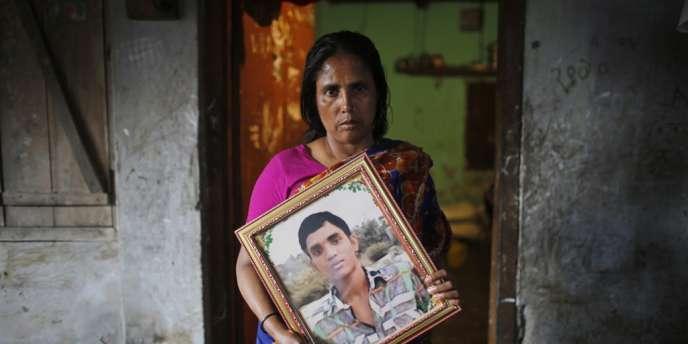 Savar, le 21 avril. Un femme pose avec le portrait de son fils, mort dans l'effondrement du Rana Plaza, en avril 2013.