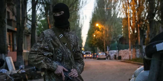Un homme armé devant le bâtiment où sont retenus les observateurs de l'OSCE à Sloviansk.