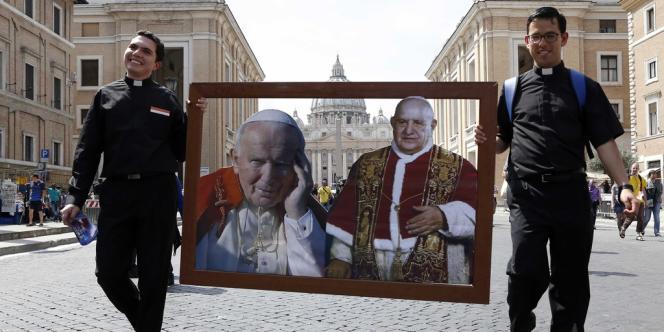 L'image des nouveaux saints, portée par deux prêtres, à Rome, près du Vatican, vendredi 25 avril.