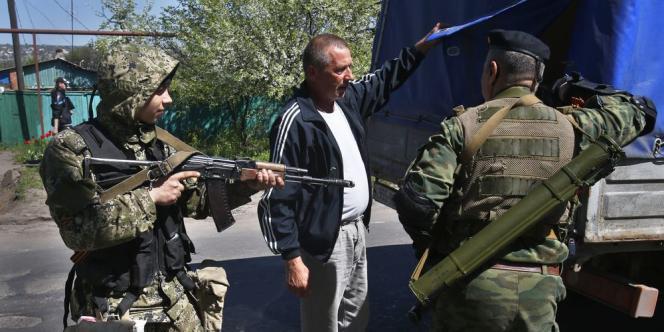 La ville de Sloviansk, bastion des séparatistes dans l'Est, est en état de siège. Ici, des hommes armés prorusses arrêtent les véhicules à l'entrée la ville, le25avril.