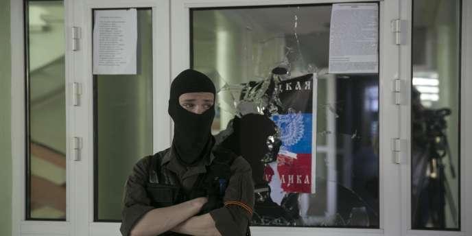 Un milicien prorusse devant la mairie de Marioupol, sur les bords de la mer Noire dans le sud-est de l'Ukraine, le 26 avril.