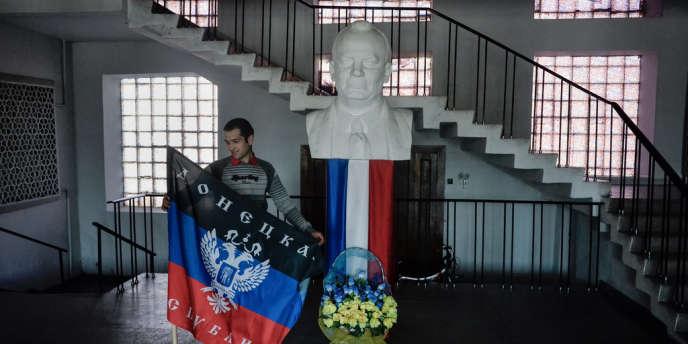 Un militant prorusse tenant dans les mains un drapeau de la République de Donetsk dans le hall de la mairie de la ville de Torez, à côté d'un portrait de Maurice Thorez.