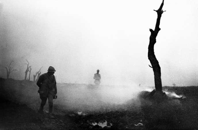 Octobre 1917, secteur de Verdun. Soldats passant près d'un arbre brûlé et de sa fumée. © Frantz Adam/AFP