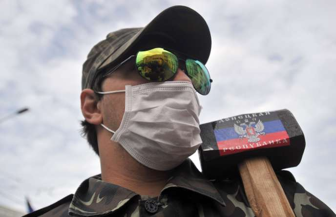 Un prorusse portant une masse arborant un drapeau de la «République de Donetsk».