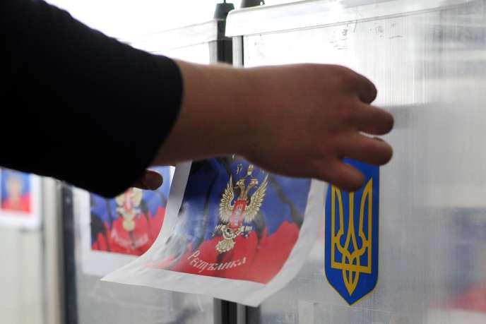 Les préparatifs du référendum: on recouvre l'emblème de l'Ukraine sur les urnes du drapeau de la république autoproclamée de Donetsk.