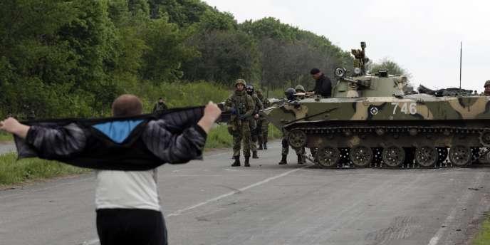 Des militaires ukrainiens face à un homme sur une route menant à Slaviansk, le 2 mai 2014.