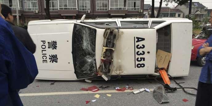 Un voiture de police gît dans une rue de Yuhang, le 10 mai, après une manifestation contre l'installation d'un incinérateur.