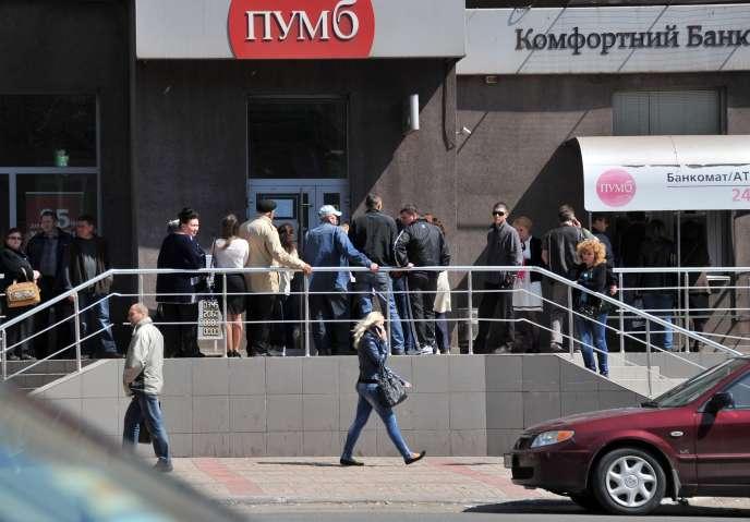 Des ukrainiens font la queue devant un distributeur de billets, à Marioupol, le 7 mai.