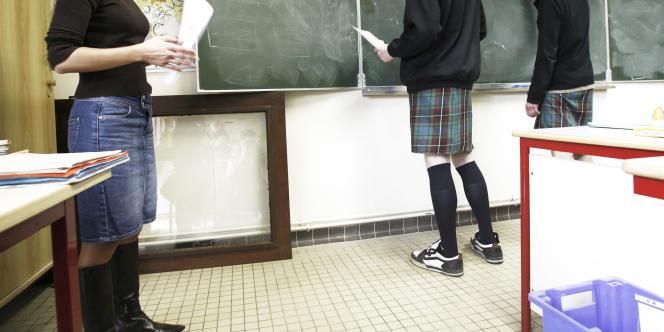 Deux garçons en kilt travaillent avec leur professeur, le 24 mars 2006 dans une classe du lycée de Saint-Aubin-du-Cormier, pendant la