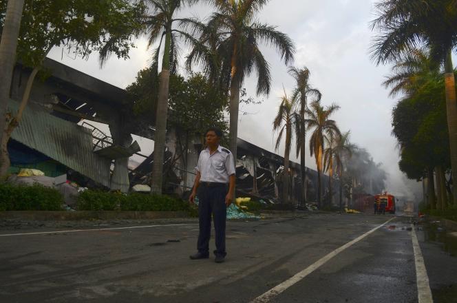 Un agent de sécurité devant une usine de confection de chaussures détruite par des émeutiers antichinois, dans la province de Binh Duong.