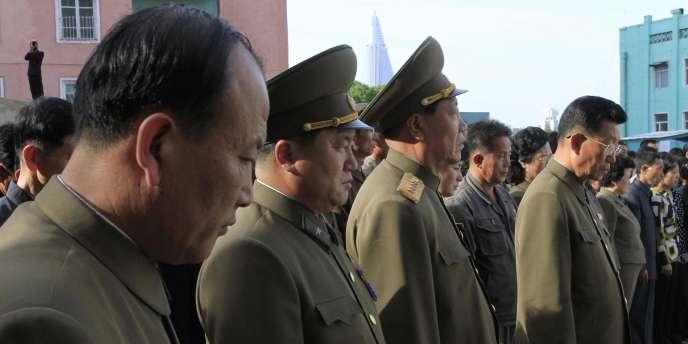 Des officiers nord-coréens avec les familles des victimes de l'effondrement de l'immeuble à Pyongyang, le 17 mai.