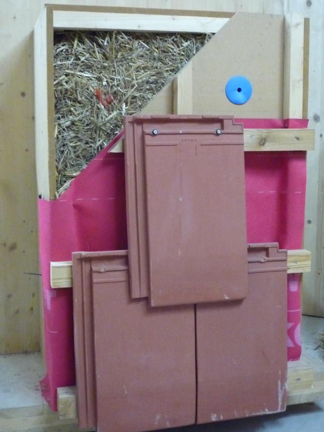 Découpe d'un caisson de paille, fixé sur la structure en bois de l'immeuble et couvert sur l'extérieur d'un bardage en tuiles de terre cuite