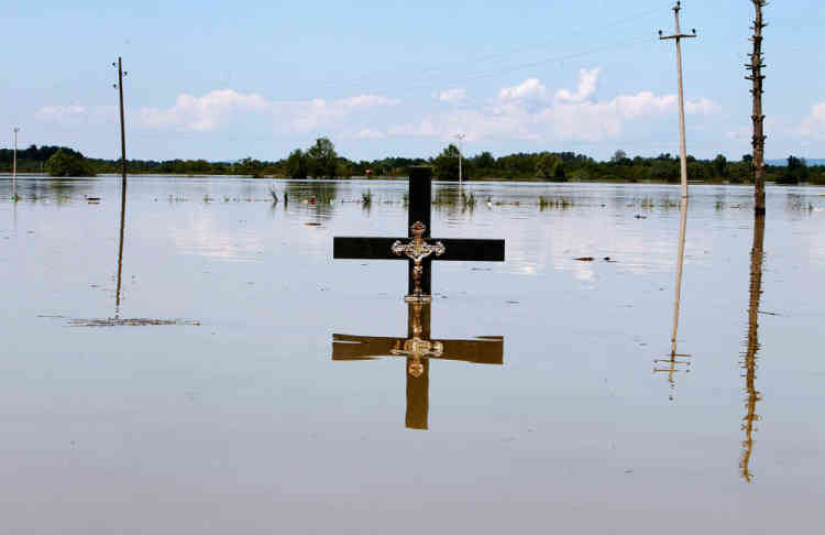 A cross is seen in floodwaters at a cemetery during heavy floods in the village of Vojskova, May 19, 2014. Communities in Serbia and Bosnia battled to protect towns and power plants on Monday from rising flood waters and landslides that have devastated swathes of both countries and killed dozens of people. REUTERS/Srdjan Zivulovic (BOSNIA AND HERZEGOVINA - Tags: DISASTER ENVIRONMENT SOCIETY)