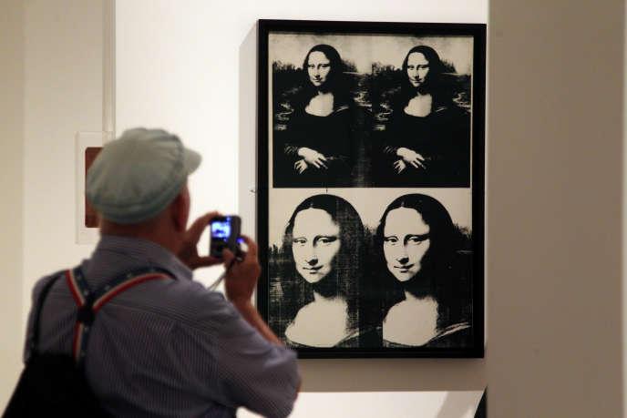 Un visiteur photographie une œuvre d'Andy Warhol représentant la Jaconde, au Metropolitan Museum of Art de New York, en septembre 2012.