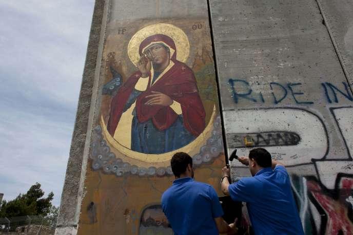 Des Palestiniens chrétiens prélèvent un bout du mur de séparation afin de l'offrir au pape, intégré dans un crucifix en bois d'olivier, le 19 mai.