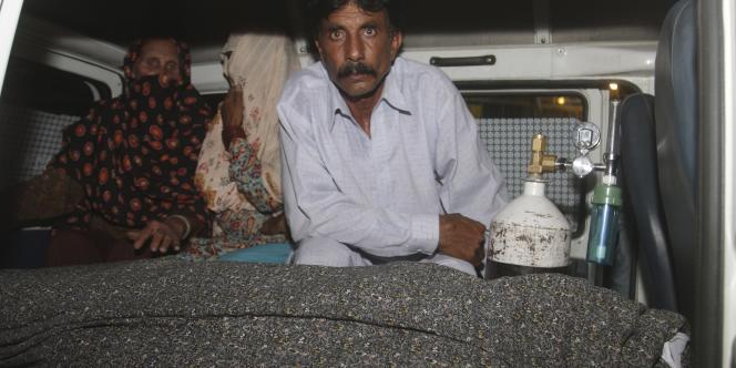 Muhammad Iqbal, dans une ambulance avec la dépouille de son épouse, Farzana Parveen, tuée par lapidation par sa famille à Lahore, au Pakistan, le 27 mai 2014.