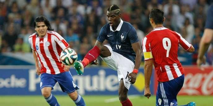 Paul Pogba face à deux Paraguayens, dimanche, à Nice.
