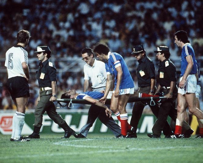 Sur la civière, Patrick Battiston, après le choc violent avec le gardien allemand Shumacher. A ses côtés, Platini lui prend le bras.