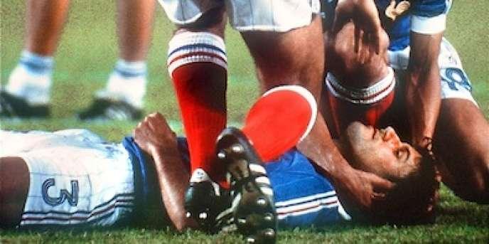 Autour de Patrick Battiston, allongé à terre, Michel Platini et et l'avant Didier Six attendent l'équipe médicale.