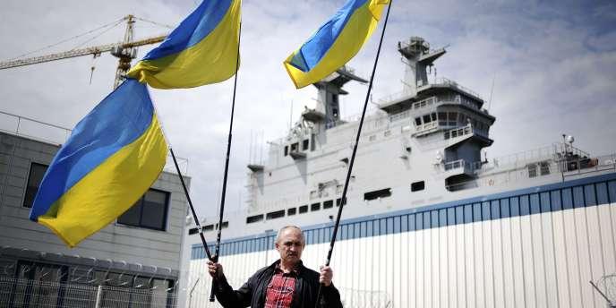 A Saint-Nazaire, le 1er juin, un manifestant brandit des drapeaux ukrainiens devant le «Vladivostok»,  un navire de guerre de type Mistral construit en France et destiné à être vendu à la Russie.