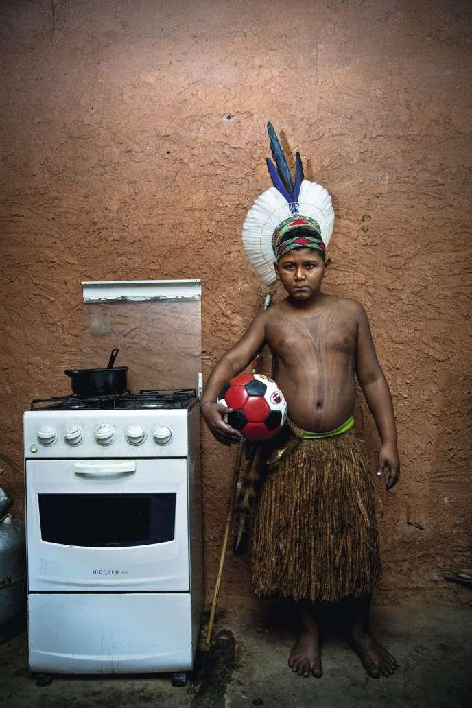 Un jeune Indien Pataxó pose avec son ballon de foot en 2013 à l'Aldeia Maracanã,  à Rio. Cette