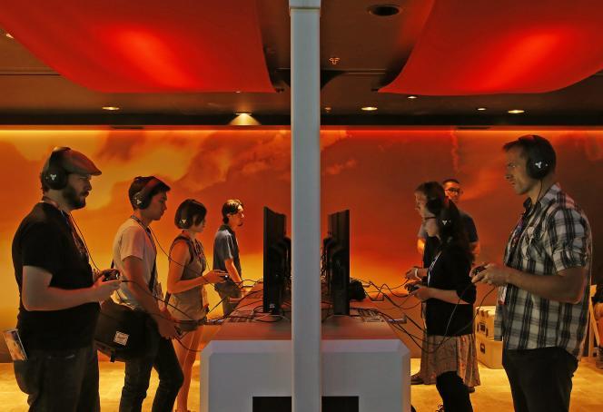 Des visiteurs de l'E3, de Los Angeles, testent de nouveaux jeux vidéo.