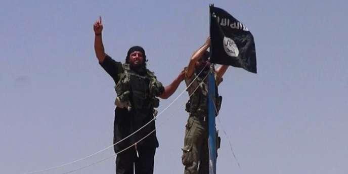 Des combattants de l'Etat islamique en Irak et au Levant (EIIL) hissent leur drapeau à un poste frontière entre l'Irak et la Syrie, le 11 juin.