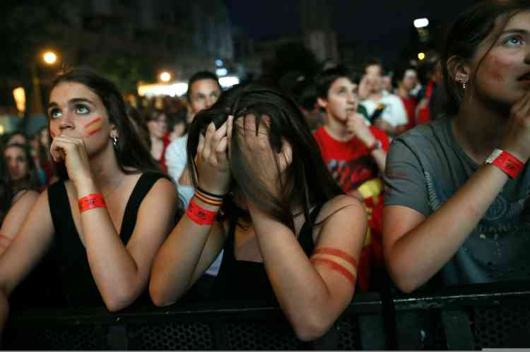 Spain supporters react as they watch the team's 2014 World Cup Group B soccer match against Netherlands on a giant screen at a fan park in Madrid, June 13, 2014. REUTERS/Juan Medina (SPAIN - Tags: SPORT SOCCER WORLD CUP)