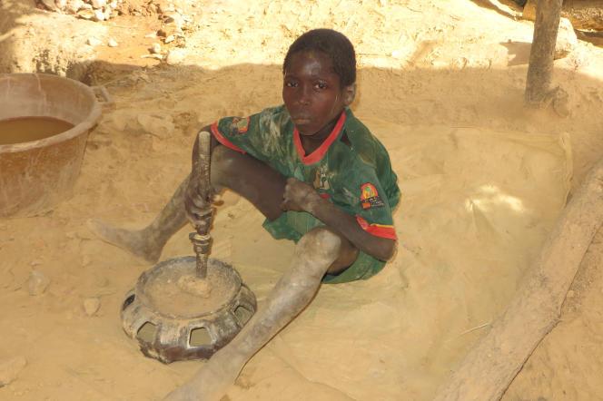 Adama, qui dit avoir 12 ans, casse du minerai pour trouver de l'or, dans le sud-est du Sénégal.