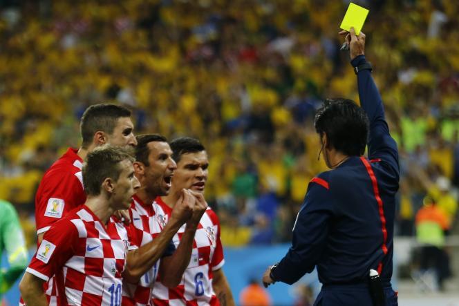 L'arbitre japonais Yuichi Nishimura assène un carton jaune au Croate Dejan Lovren, lors du match d'ouverture entre le Brésil et la Croatie, jeudi 12 juin.