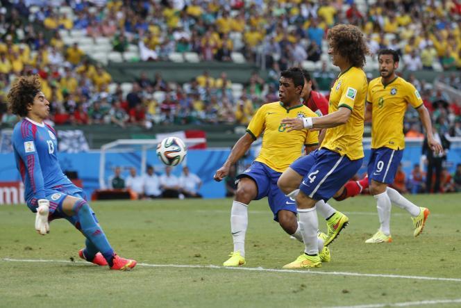 Pour sa troisième participation à la Coupe du monde, Guillermo Ochoa s'est montré intraitable face aux Brésiliens, ici Paulinho et David Luiz, mardi 17 juin, à Fortaleza.