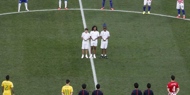 Les trois enfants invités à lâcher des colombes lors de la cérémonie d'ouverture le 12 juin. A droite, le jeune Weka Mirim.