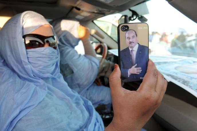 Une Mauritanienne montre un portrait de Mohamed Ould Abdel Aziz sur son téléphone portable, le 18 juin, à Akjoujt.