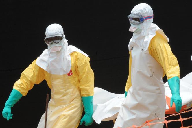 Des médecins transportent des corps de victimes du virus Ebola, le 1er avril à Gueckedou, en Guinée.
