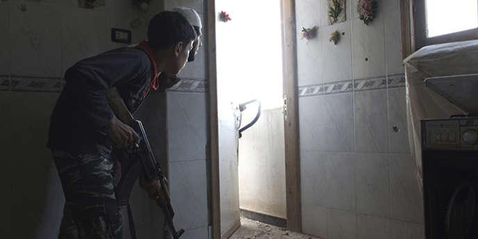 Un jeune combattant de la brigade de l'Armée syrienne libre, âgé de 14 ans, prend position à l'intérieur d'une maison à Deir Ez-Zor, dans l'est de la Syrie, en juillet 2013.