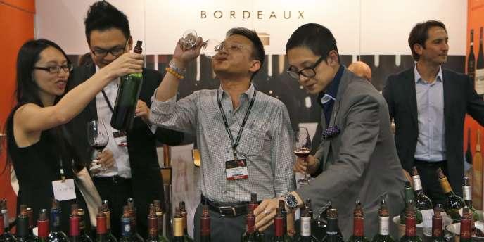 Des visiteurs goûtent du vin au salon Vinexpo de Hongkong, le 28 mai.