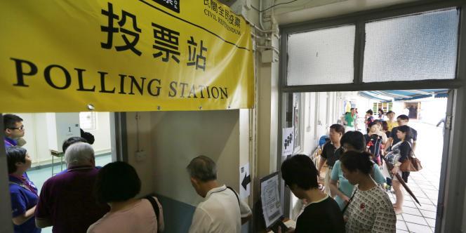Des Hongkongais font la queue devant un bureau de vote pour participer au référendum citoyen sur le mode de désignation du chef de l'exécutif du petit territoire du sud de la Chine, le29juin2014.