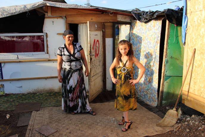 Une mère et sa fille sur leur trente-et-un, devant leur baraque sur le terrain de la Folie, à Grigny, le 2 juillet 2014. Le chiffre sur la porte indique le nombre d'occupants.